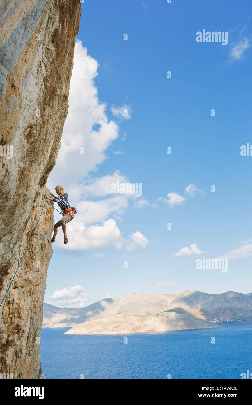Greece, Dodecanese, Kalymnos, Rock climber on steep cliff - Stock Image