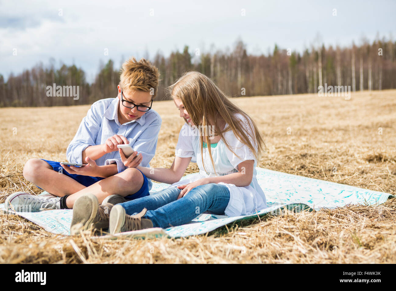 Finland, Keski-Suomi, Aanekoski, Girl (12-13) and boy (12-13) sitting on blanket in field and looking on mobile - Stock Image