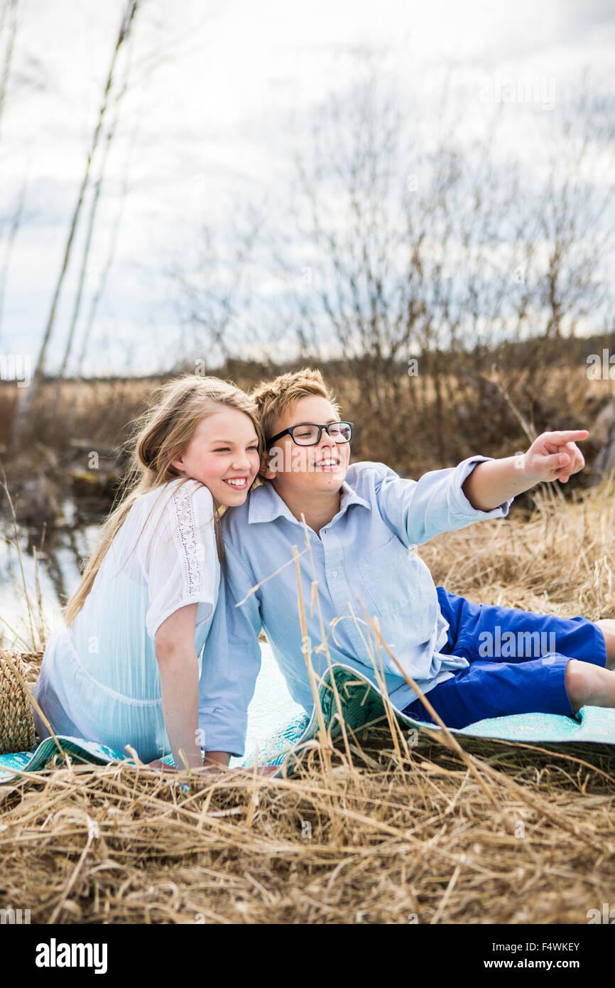 Finland, Keski-Suomi, Aanekoski, Girl (12-13) and boy (12-13) sitting on blanket outside and looking away - Stock Image