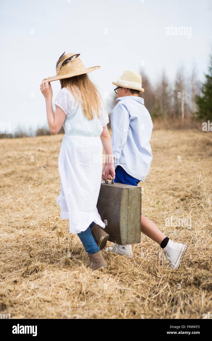 Finland, Keski-Suomi, Aanekoski, Girl (12-13) and boy (12-13) walking in field and carrying suitcase - Stock Image