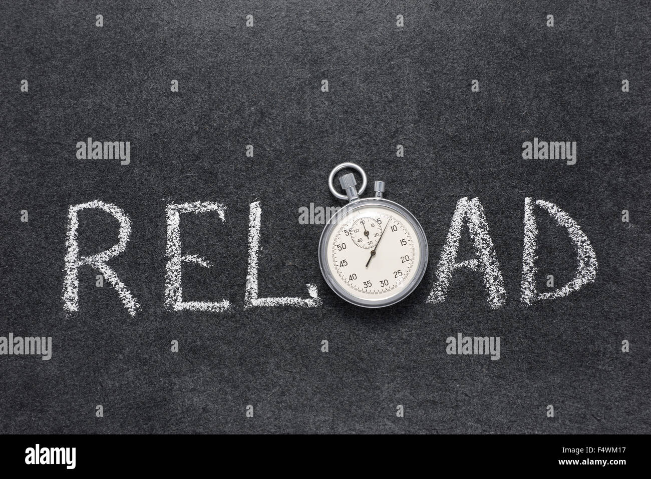 reload word handwritten on chalkboard with vintage precise stopwatch used instead of O - Stock Image