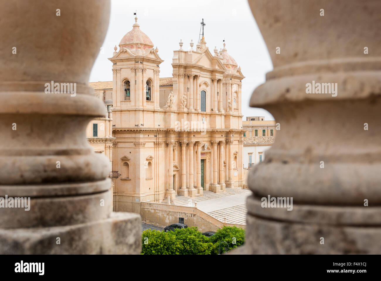 The baroque cathedral of Noto (UNESCO site in Sicily), seen through two columns - Stock Image