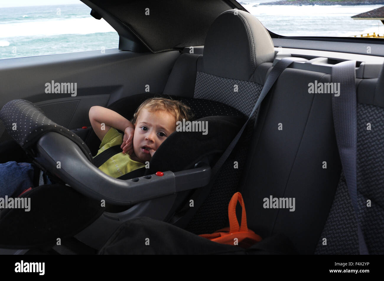 Child in a baby seat rear of a Rental car Chrysler Sebring Stock ...