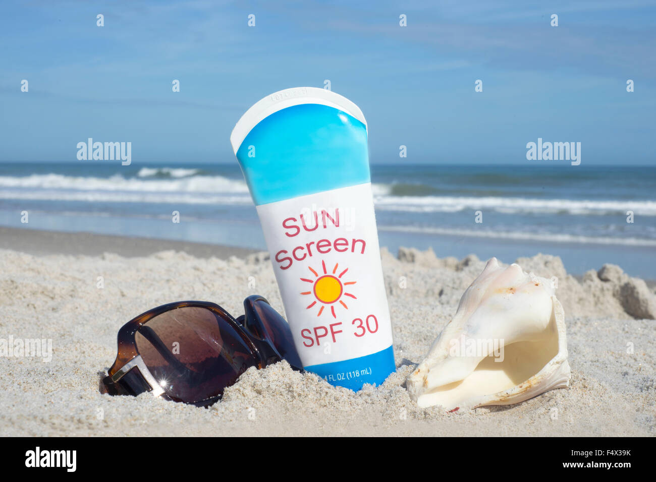 Bottle of sunscreen with shell and sunglasses on beach. - Stock Image