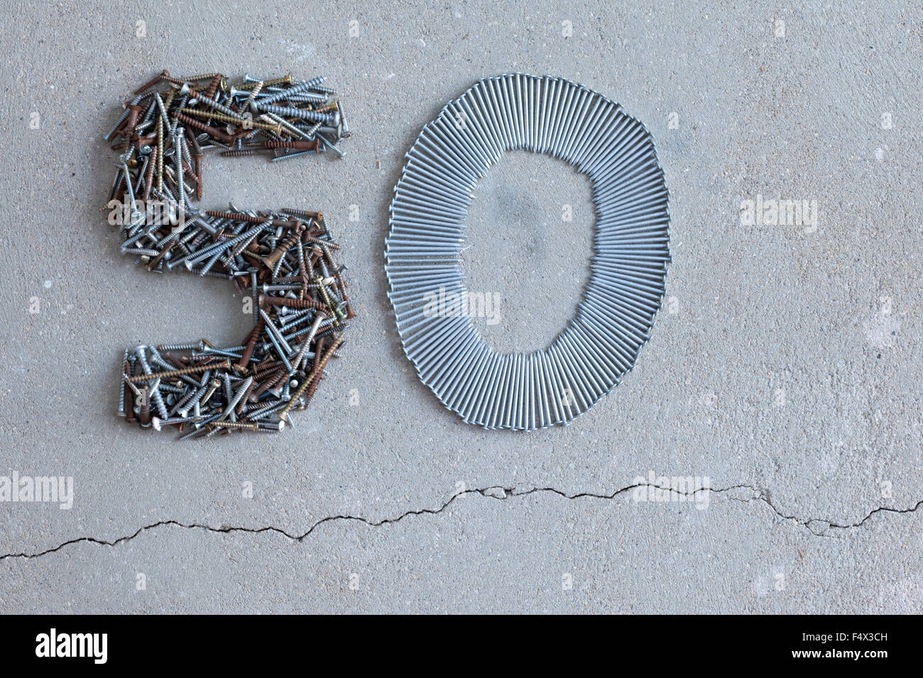 50 fifty number arranged out of old screws and nails on a concrete floor - Stock Image