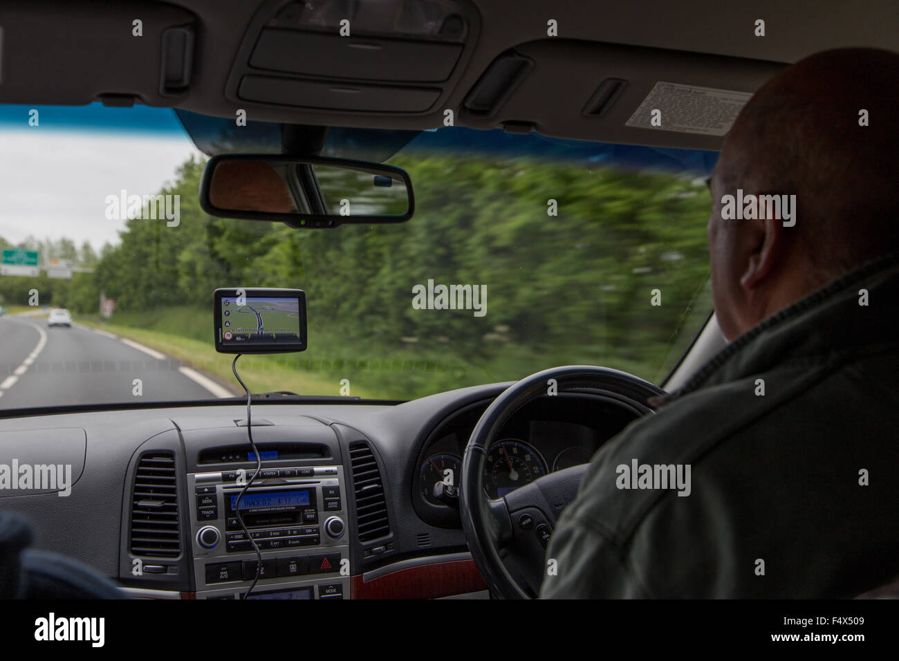 Male driver using a sat nav (satellite navigation device) on a main road in UK - Stock Image