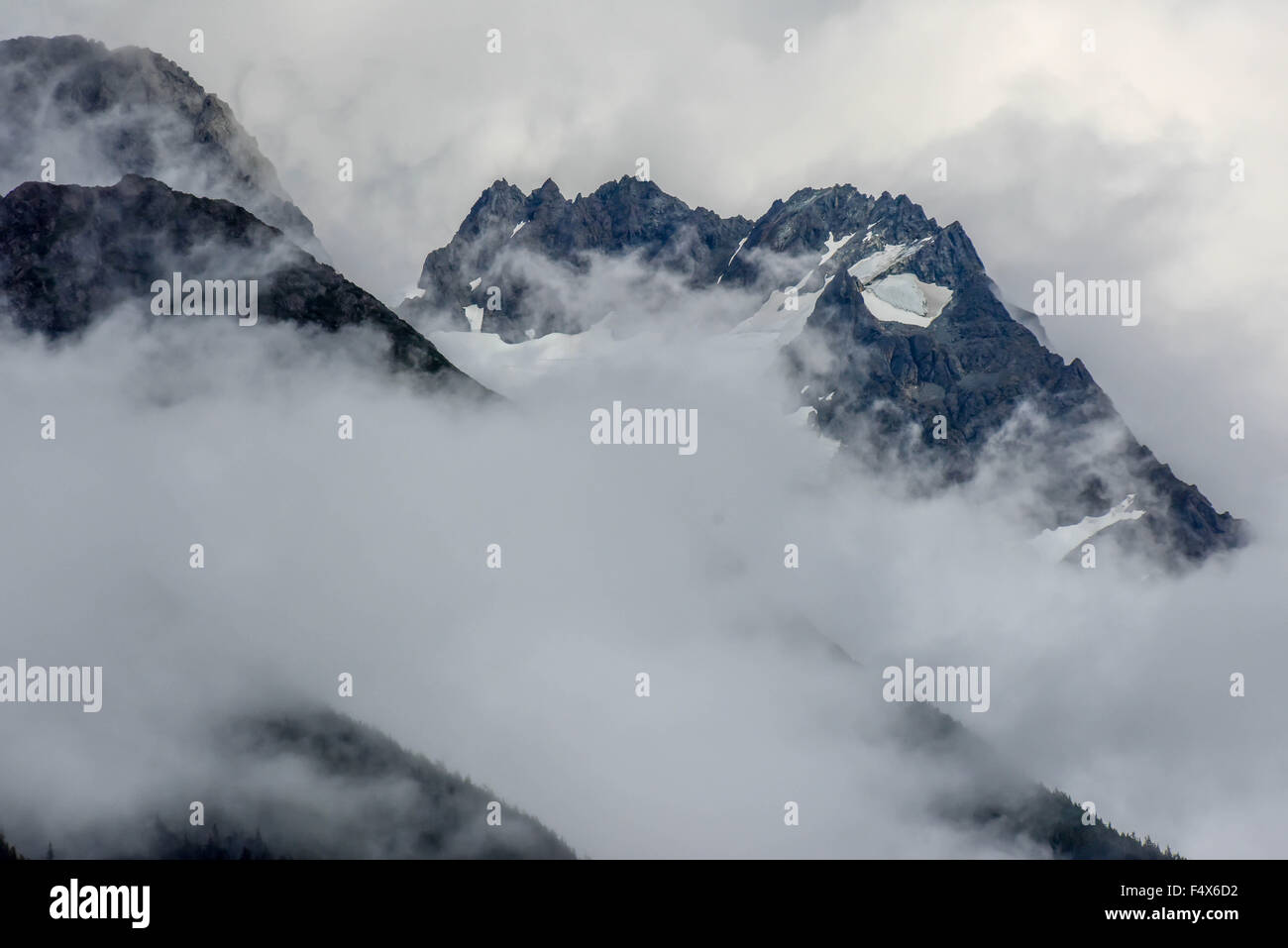 Hanging glaciers and clouds on the mountain tops near port of Skagway Alaska | Lynn Canal fjord cruise - inside - Stock Image