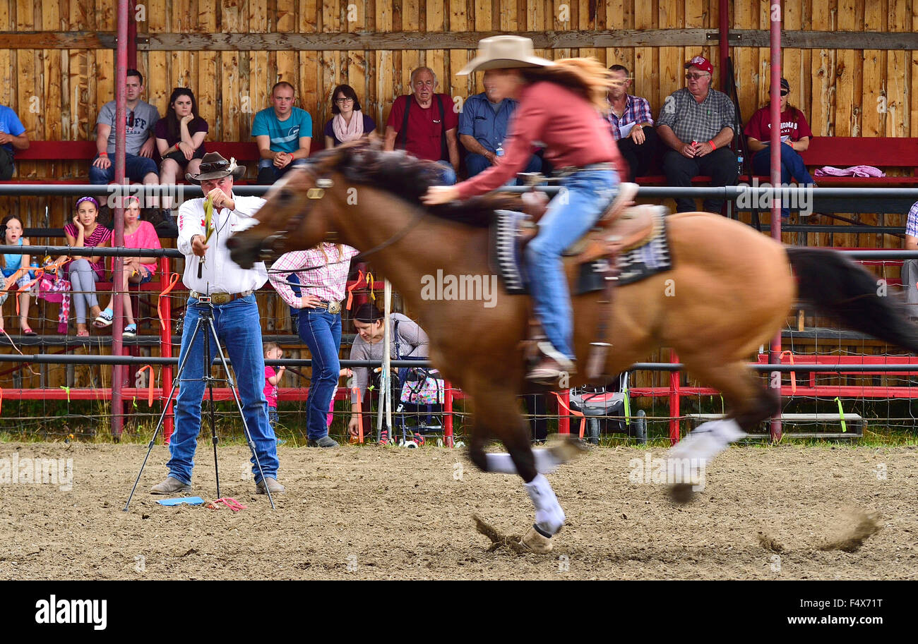 A lady barrel racer dashes for the finish line at a rodeo event in rural Alberta Canada - Stock Image
