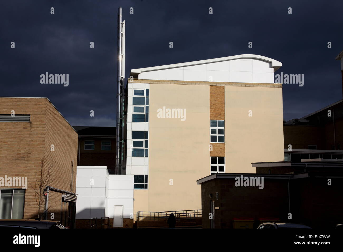 A starkly contrasting picture of a bright building in sunlight and a very dark and ominous background. - Stock Image