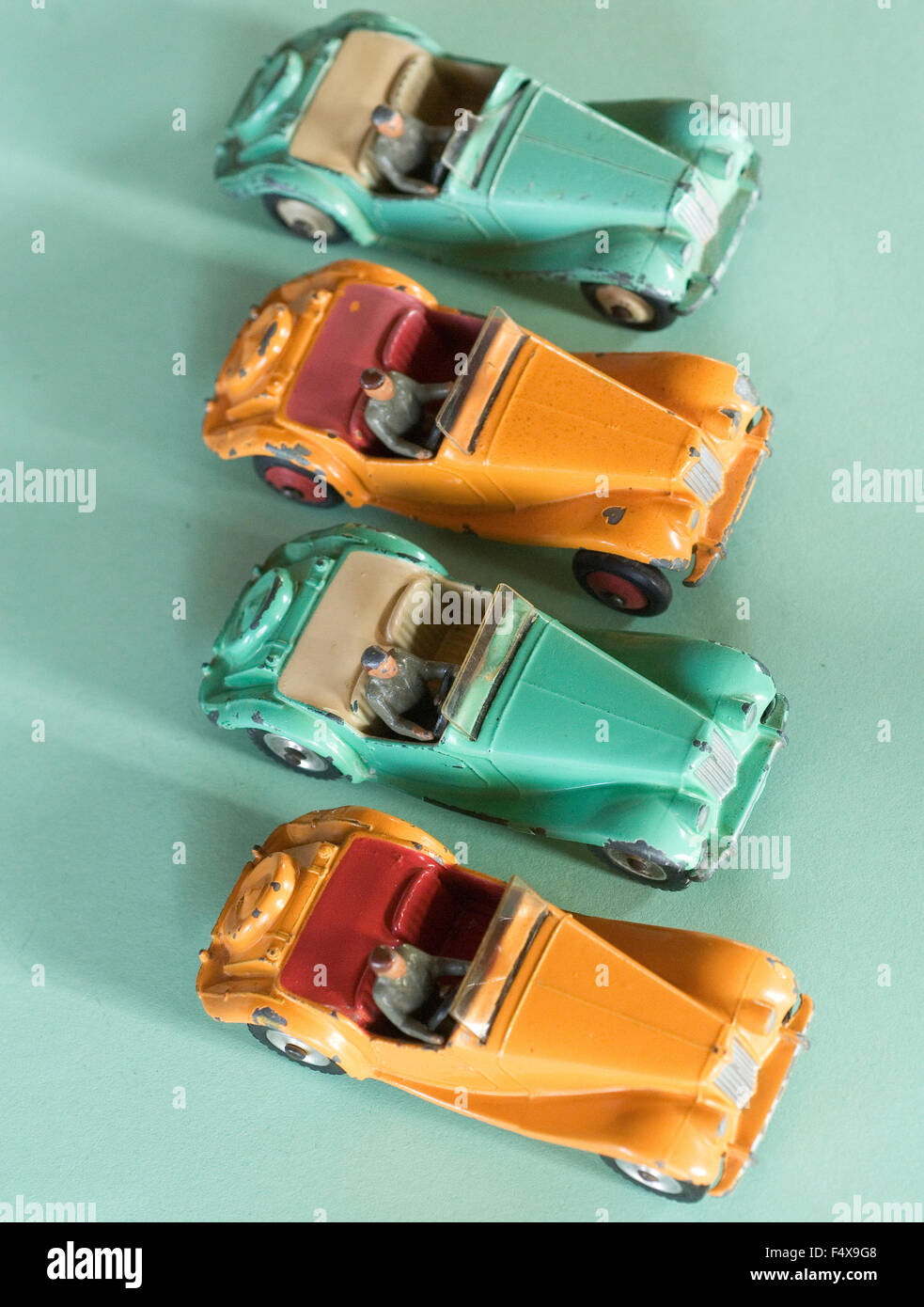 Four dinky sports cars in a row. MG's Orange and Green. - Stock Image