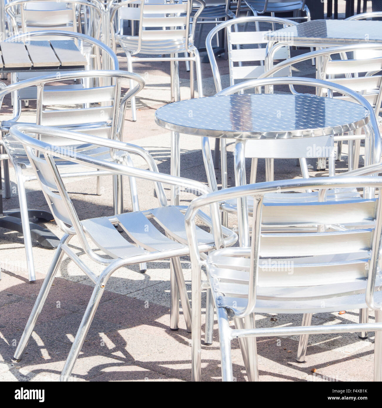 seats metallic reflection. several tables and metal chairs empty - Stock Image