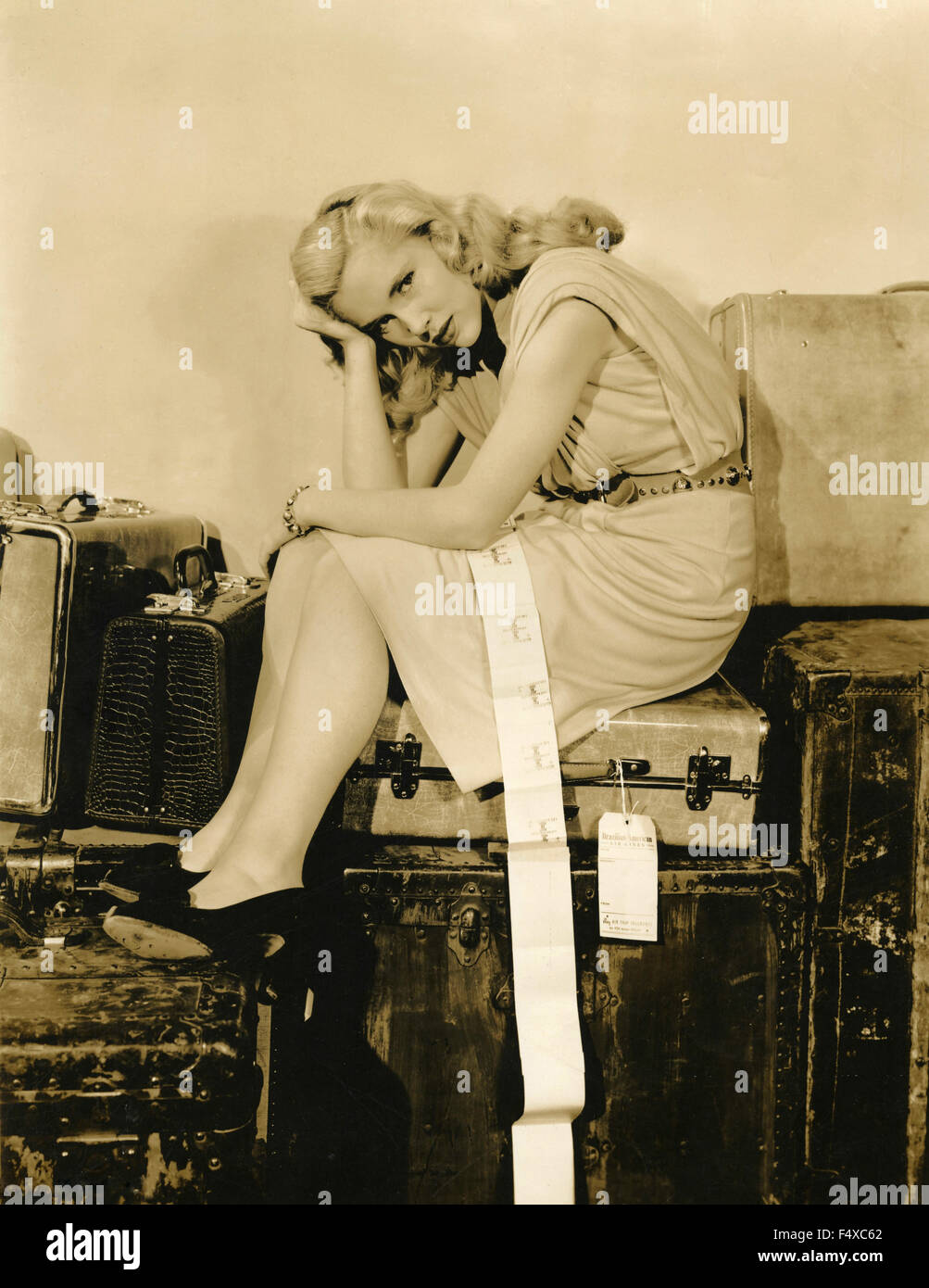 American actress Sally Forrest sitting on a pile of suitcases, USA - Stock Image