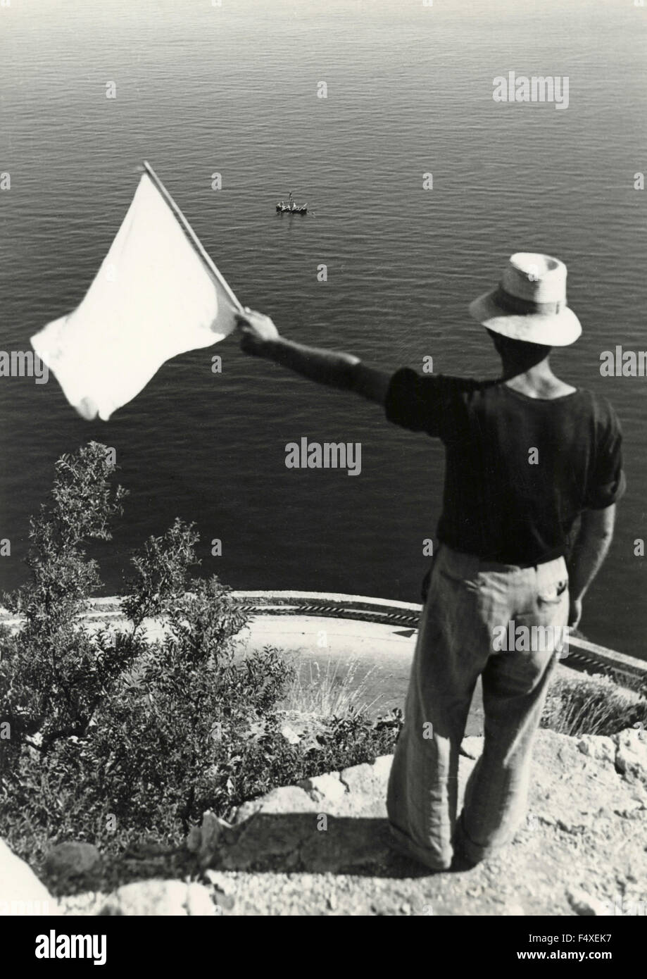 A man with a flag indicates the sighting while fishing for swordfish, Calabria, Italy - Stock Image