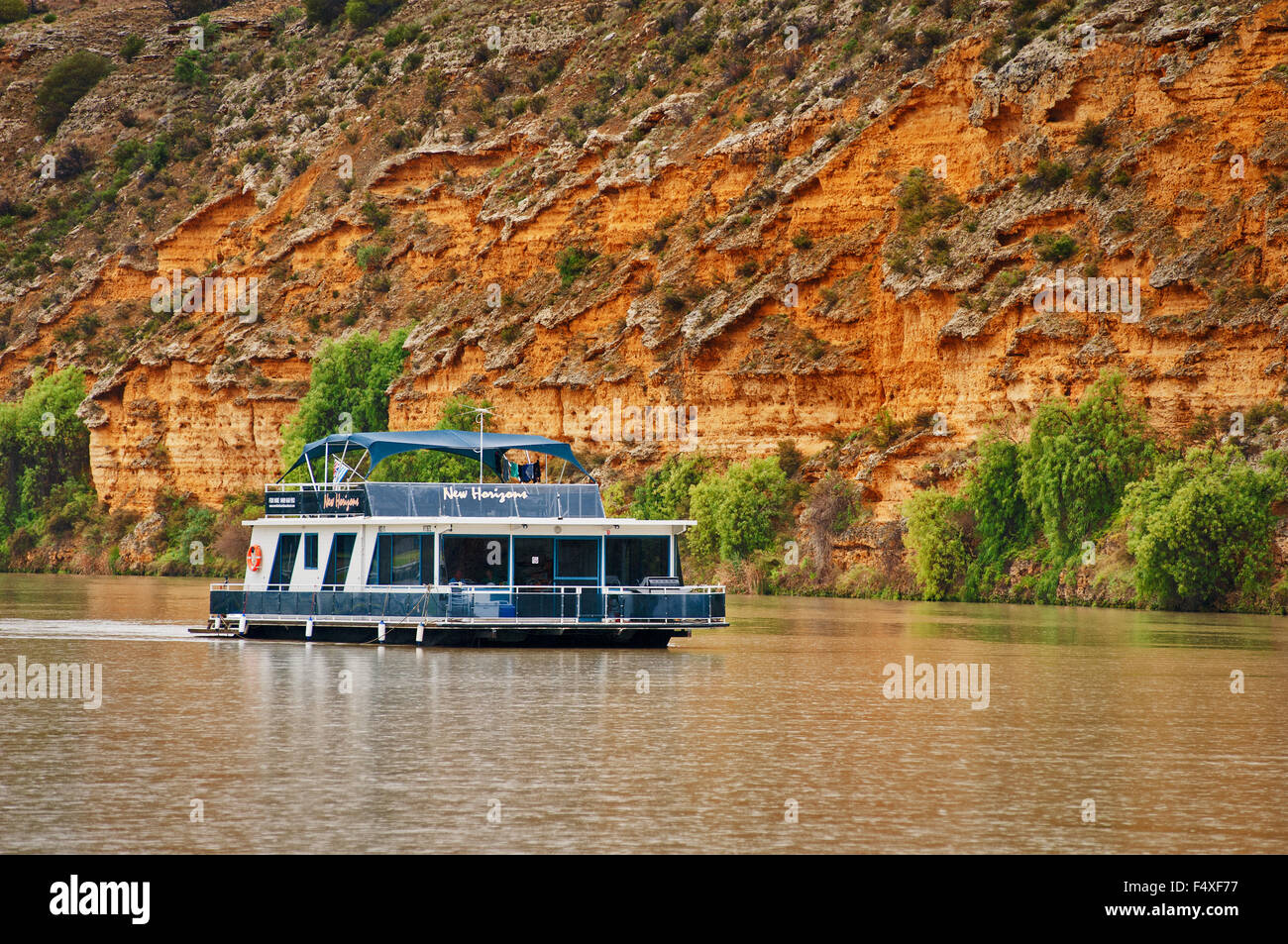 Houseboat cruising on Murray River in front of high cliffs. Stock Photo