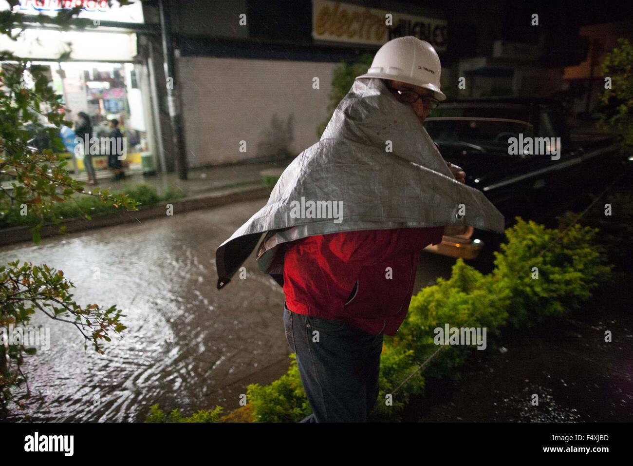 """Ameca, Mexico. 23rd Oct, 2015. A man protects himself from the rain caused by the hurricane """"Patricia"""" in Ameca, Stock Photo"""