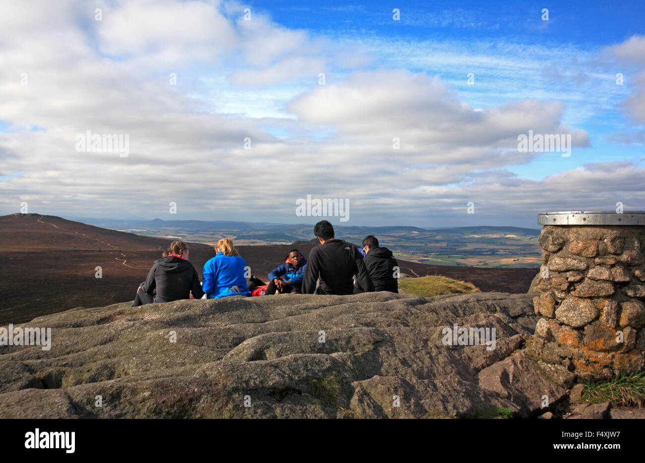 A group of hill walkers picnicking on the summit of Mither Tap, Bennachie, Aberdeenshire, Scotland, United Kingdom. - Stock Image