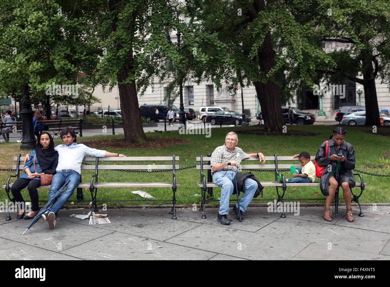 people of several races sit on bench in downtown manhattan new york city near city hall and brooklyn bridge - Stock Image