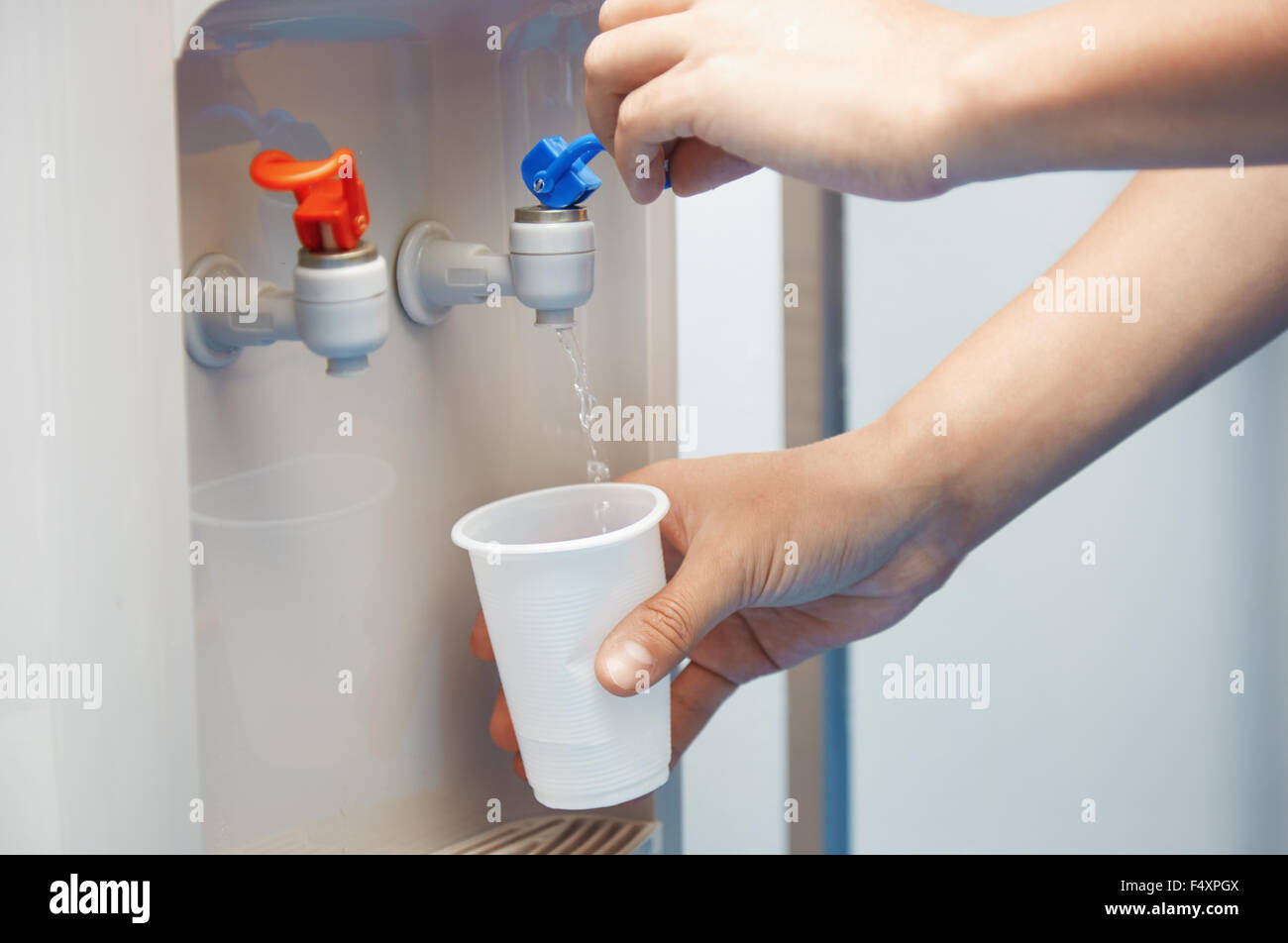 Man filling plastic cup at water cooler - Stock Image