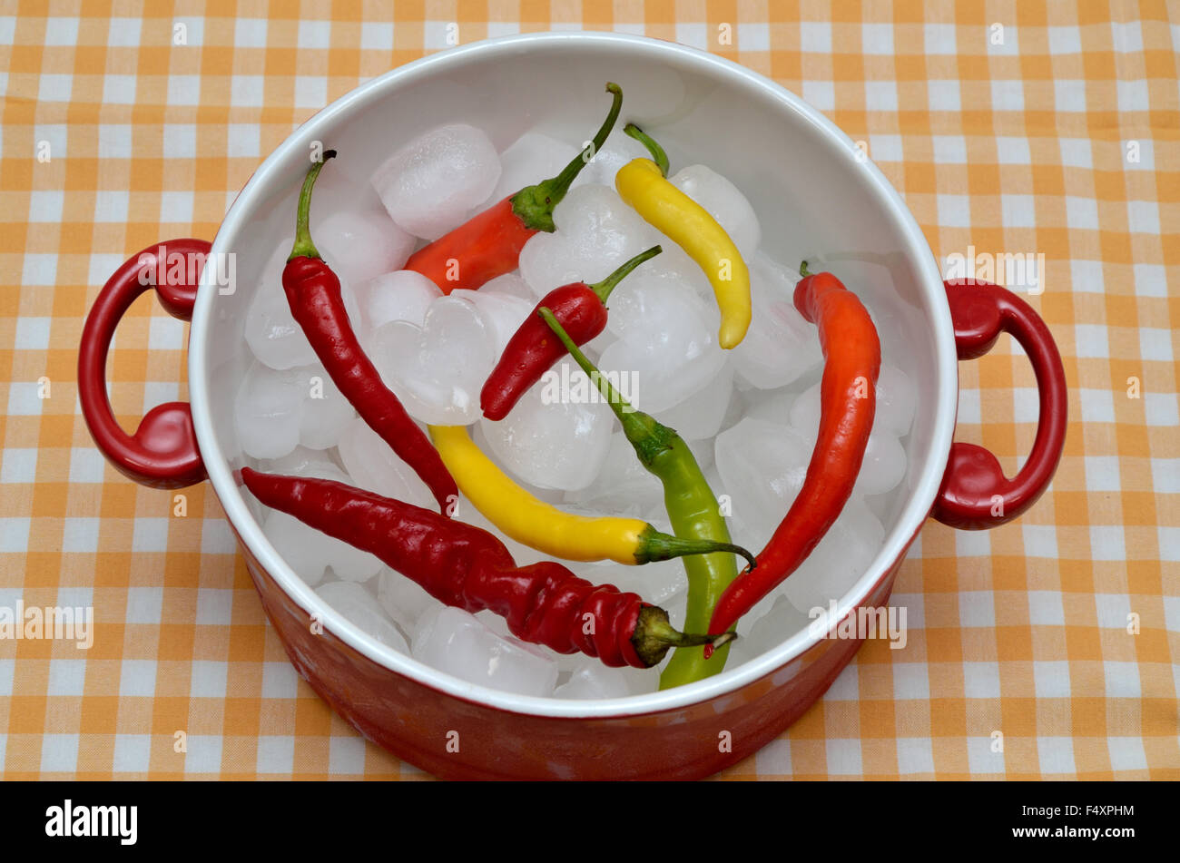 Red, Orange, Green And Yellow Hot Chili Peppers In Red Casserole Full Of  Ice Cubes   On White Yellow Tablecloth