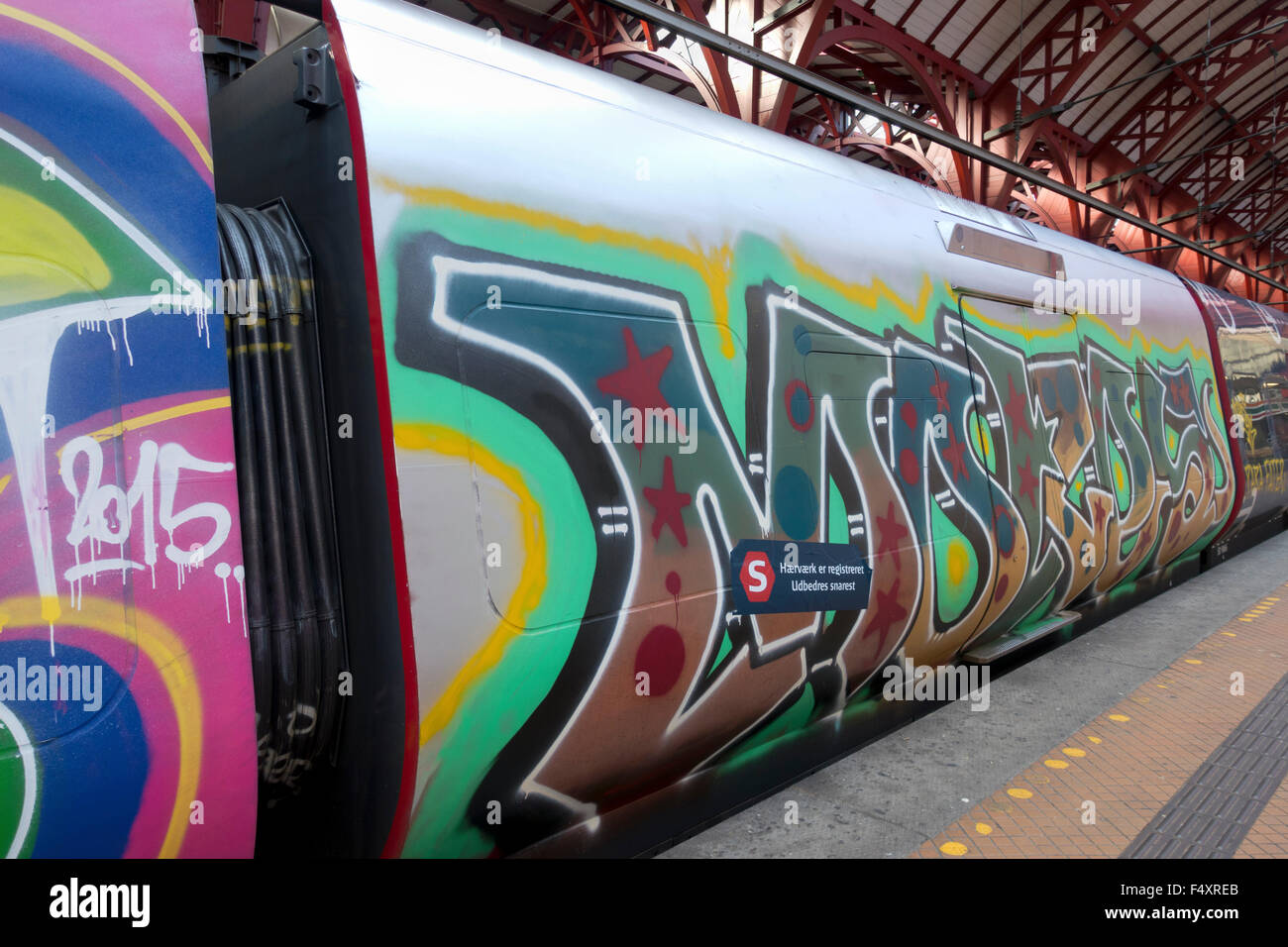 Graffiti totally vandalises this S-train carriage. Train  at platform at Copenhagen Central Station and still in - Stock Image