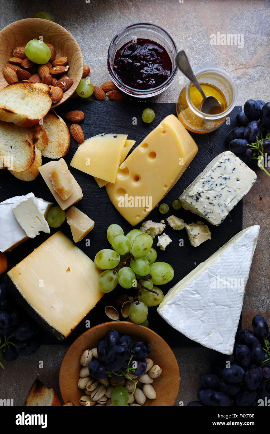 delicatessen cheeses with fruits, top view - Stock Image