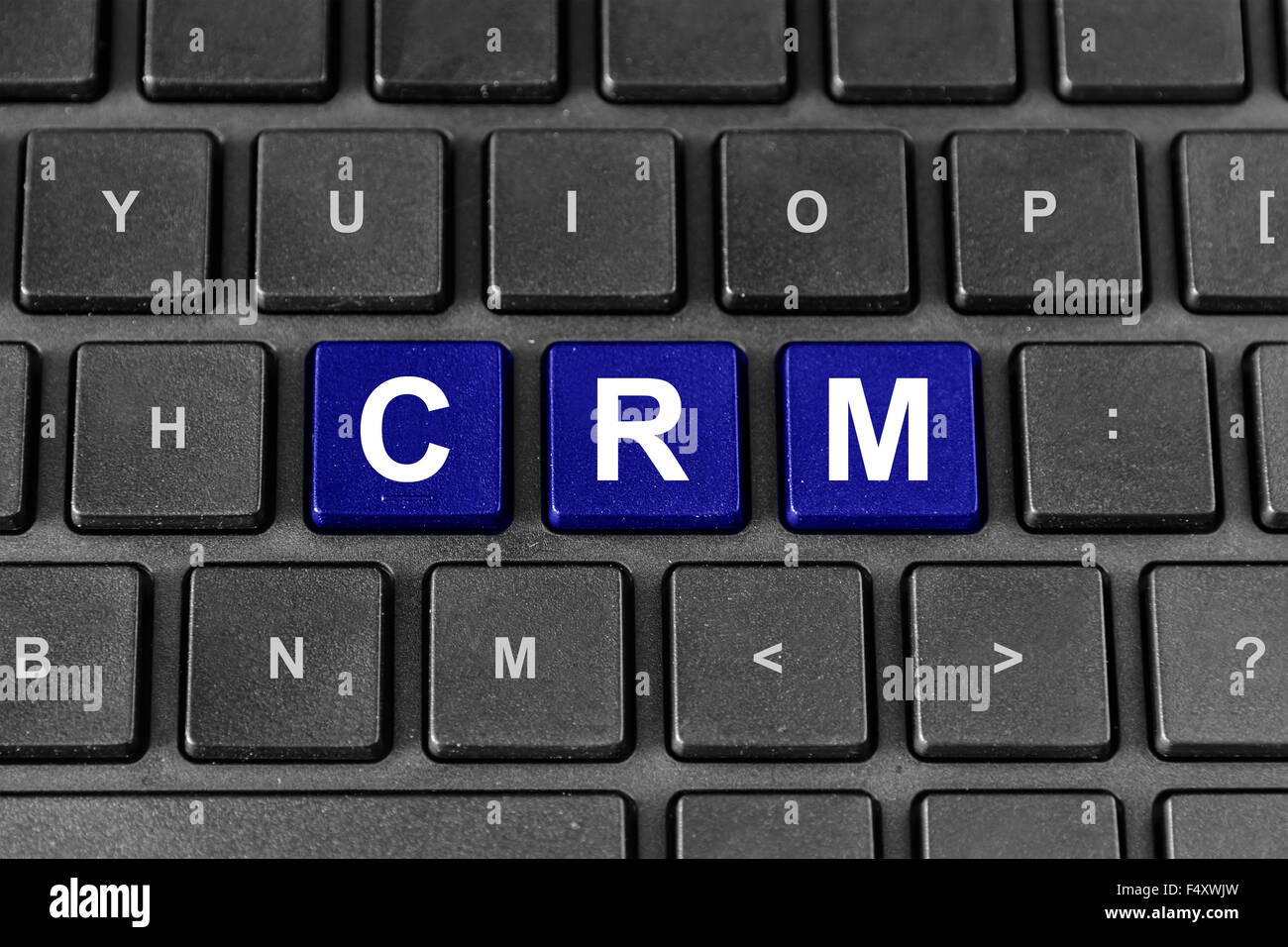 CRM or Customer relationship management blue word on keyboard - Stock Image