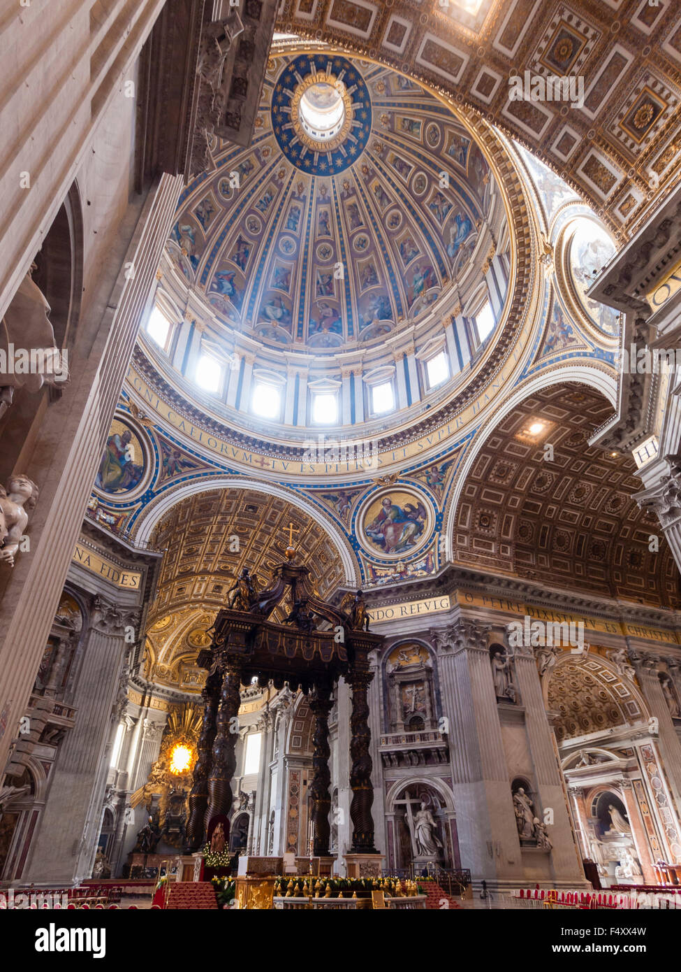 Interior of the Papal Basilica of St. Peter, Vatican: chancel with Bernini's baldacchino altar underneath the - Stock Image