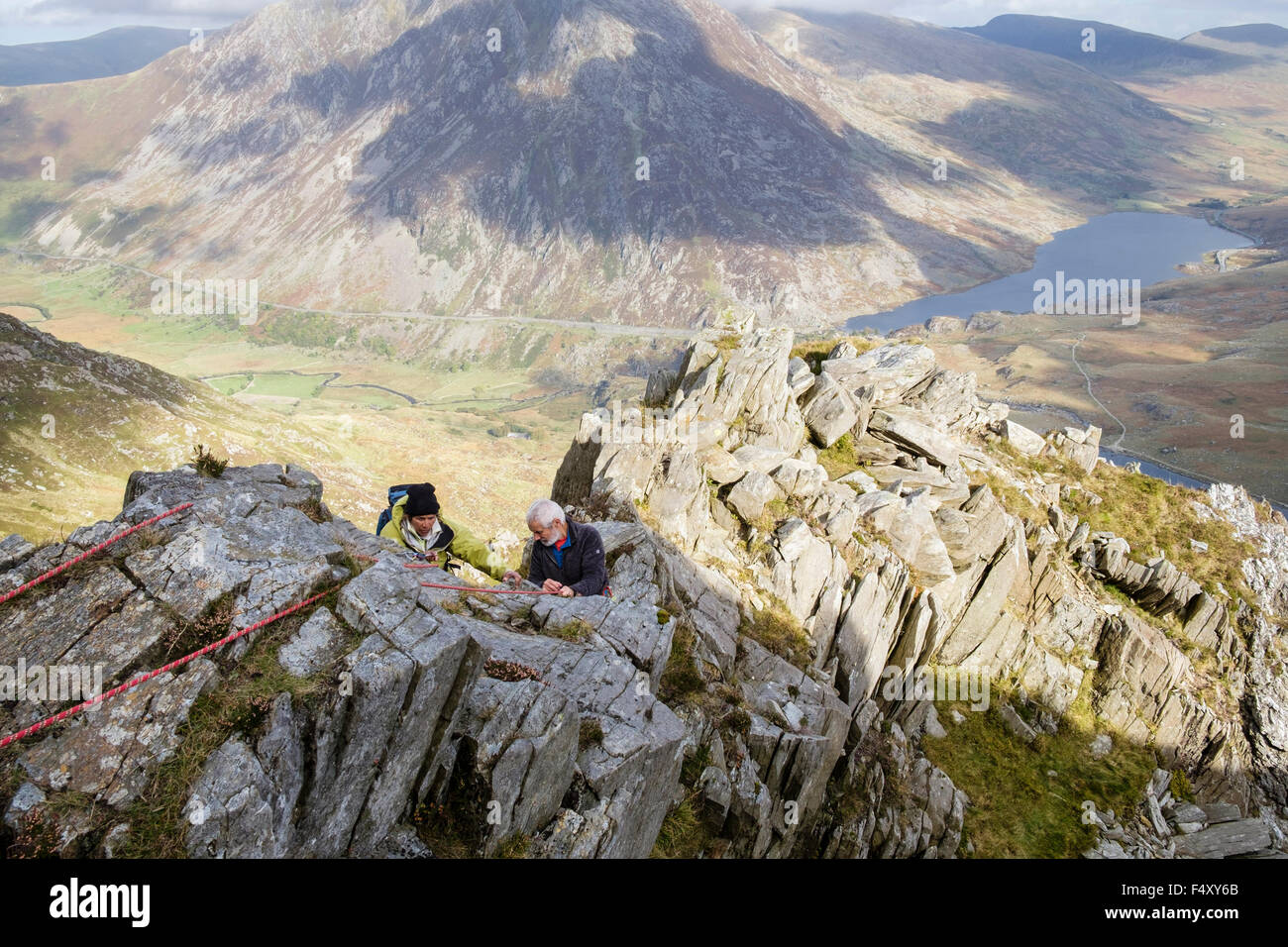 Hikers scrambling using a safety rope on Y Garn north east ridge high above Ogwen Valley in mountains of Snowdonia - Stock Image