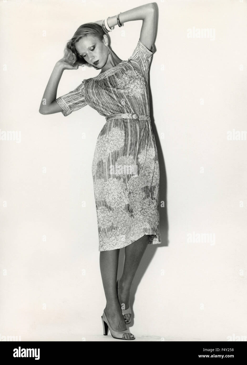 A model wears a dress fabric printed with stripes and flowers - Stock Image
