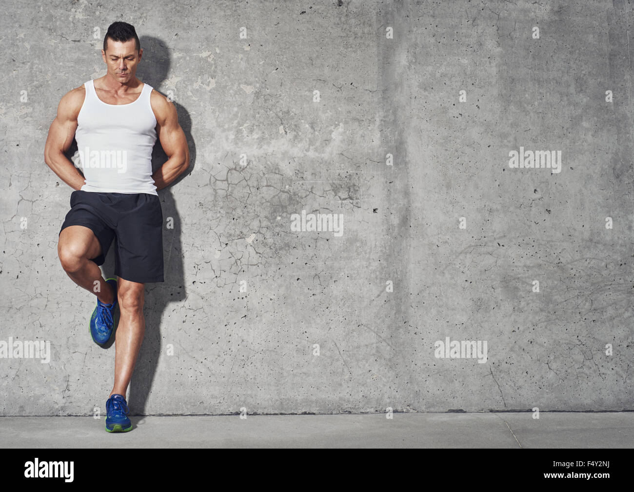 Fit and healthy man, muscular build portrait, fitness concept with copy space on grey background - Stock Image