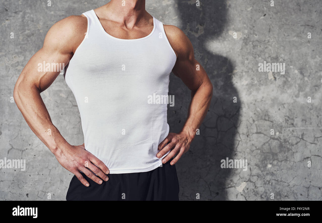 Close up fitness portrait of white muscular man in white tank top, standing on grey background, copy space, fitness - Stock Image
