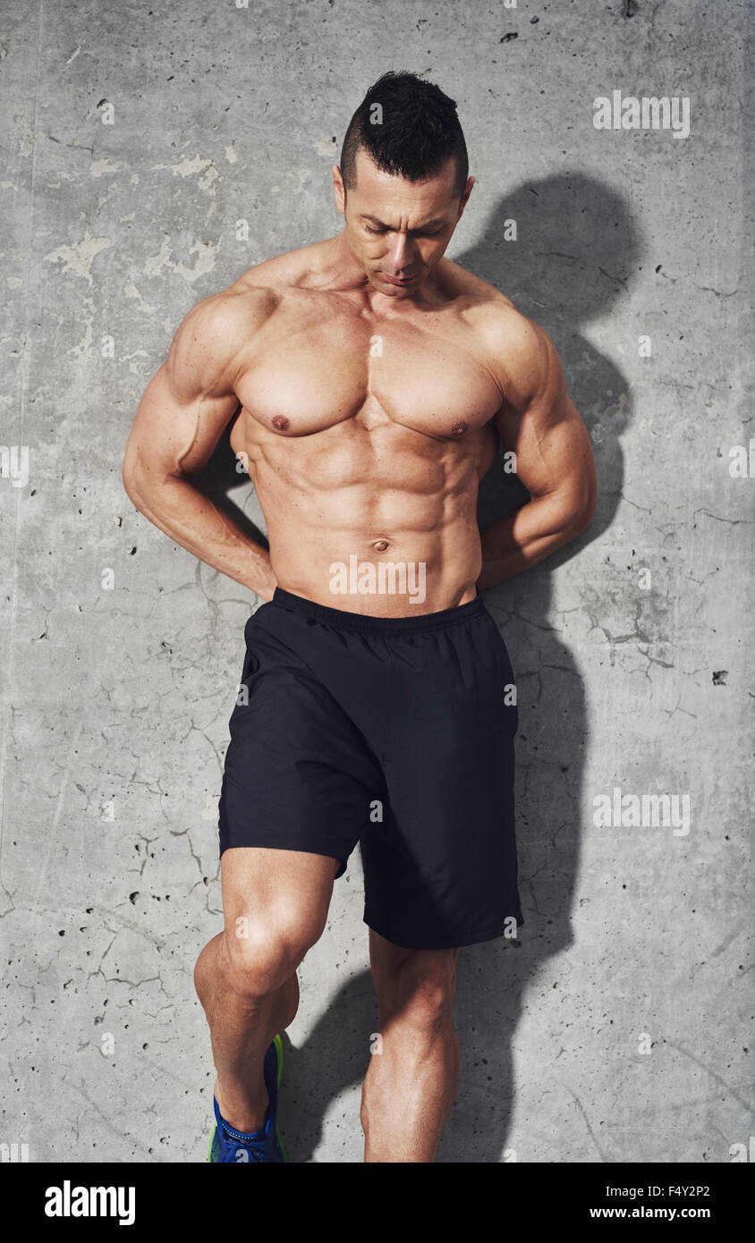 Muscular fit and healthy man standing on grey background, looking down, wearing no shirt and black shorts. Fitness - Stock Image