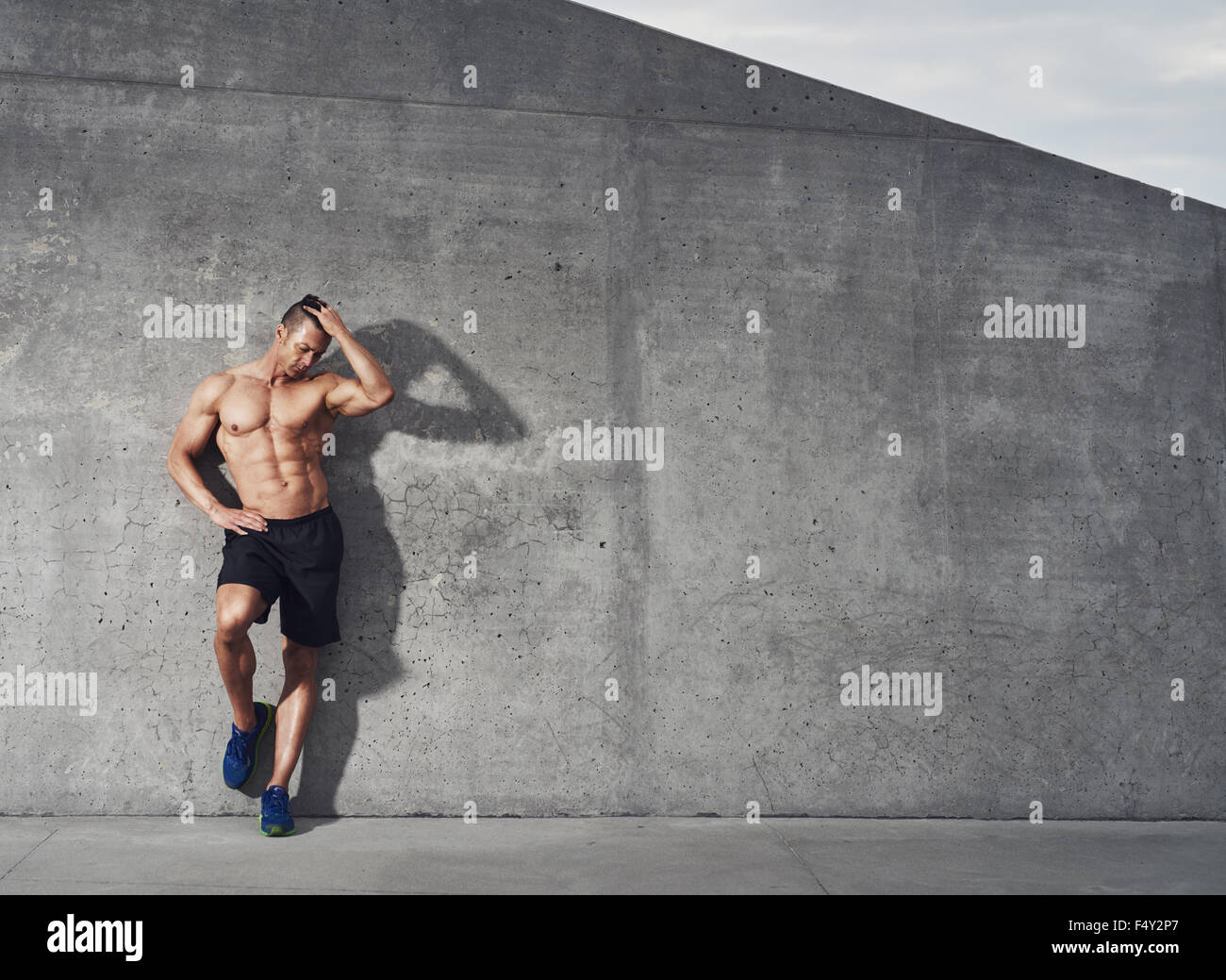 Fit and healthy male fitness model portrait, standing against wall looking down, room for copy space. - Stock Image