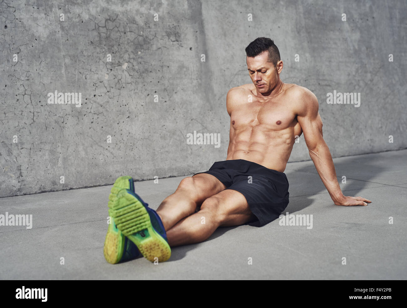 Muscular man relaxing after workout, while wearing no shirt showing abdominal six pack and looking relaxed - Stock Image