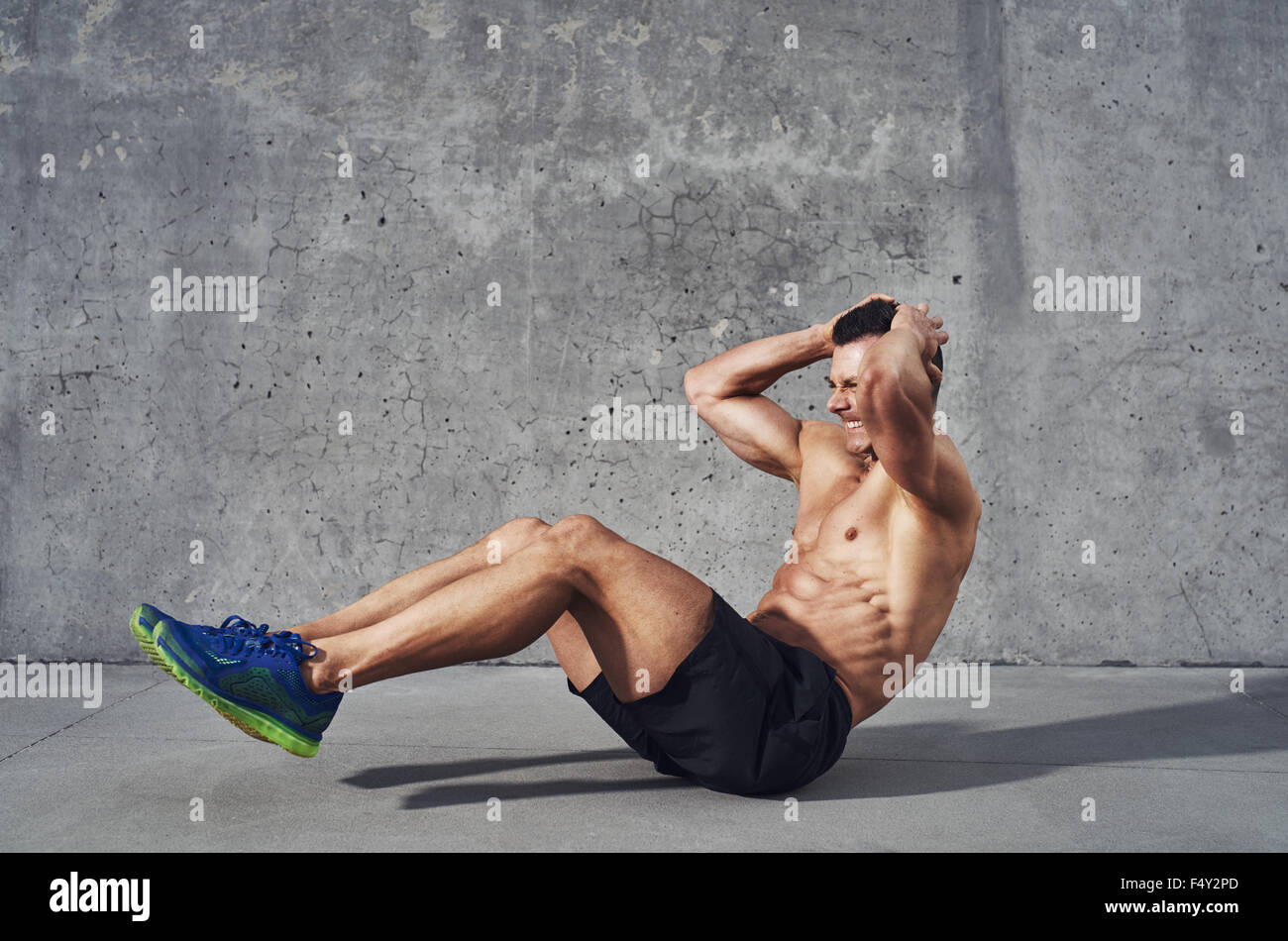 Fitness model exercising sit ups and crunches. Muscular well build, toned body with six pack sweating. Copy space - Stock Image