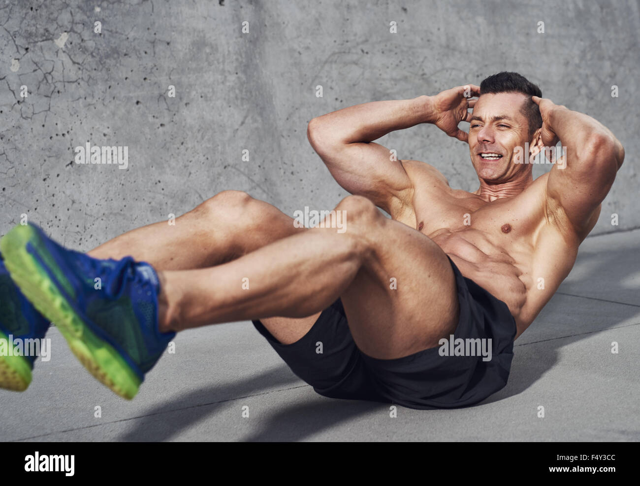 Muscular male fitness athlete doing sit ups, Clean look on grey background, visible no shirt - Stock Image