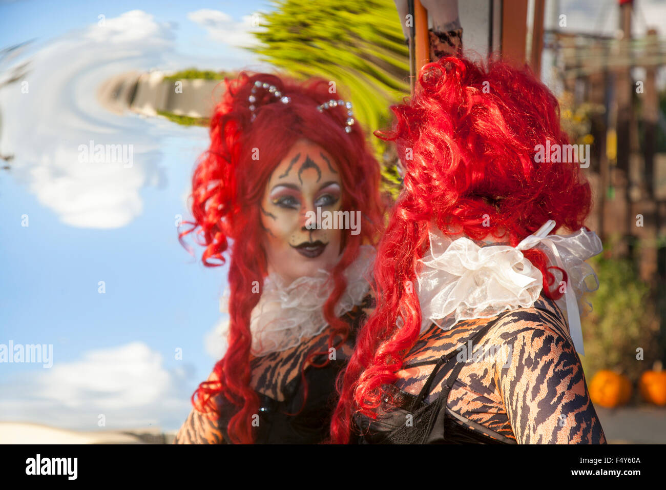 Woman with red hair wig, in cat suit with fun and interesting reflected images in distorting convex & concave - Stock Image