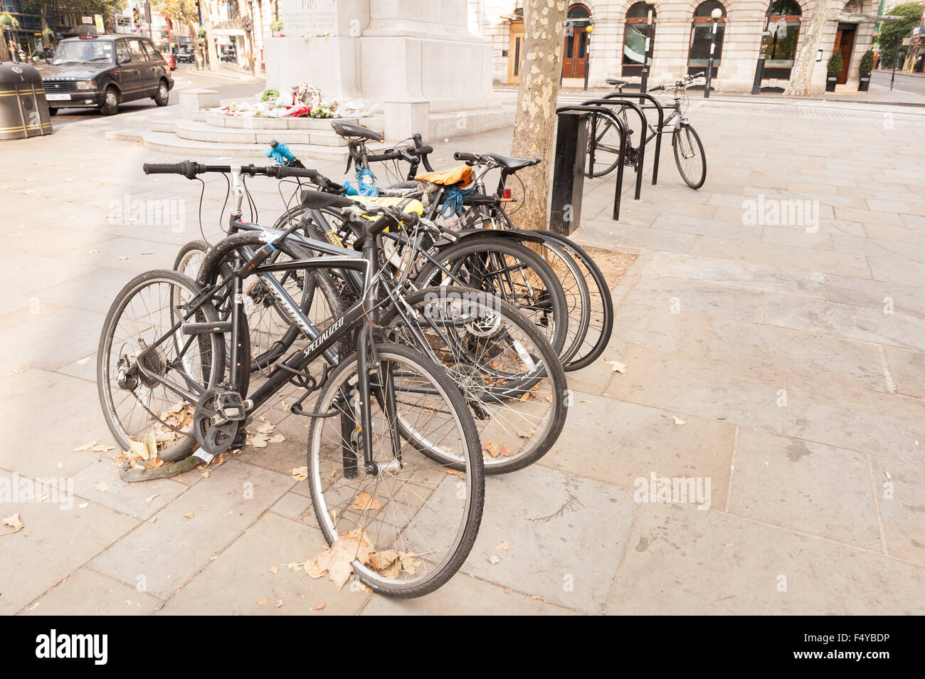 Massive numbers of bikes chained up on trees racks in center of flagstone pavement Trafalgar Square Postoffice - Stock Image