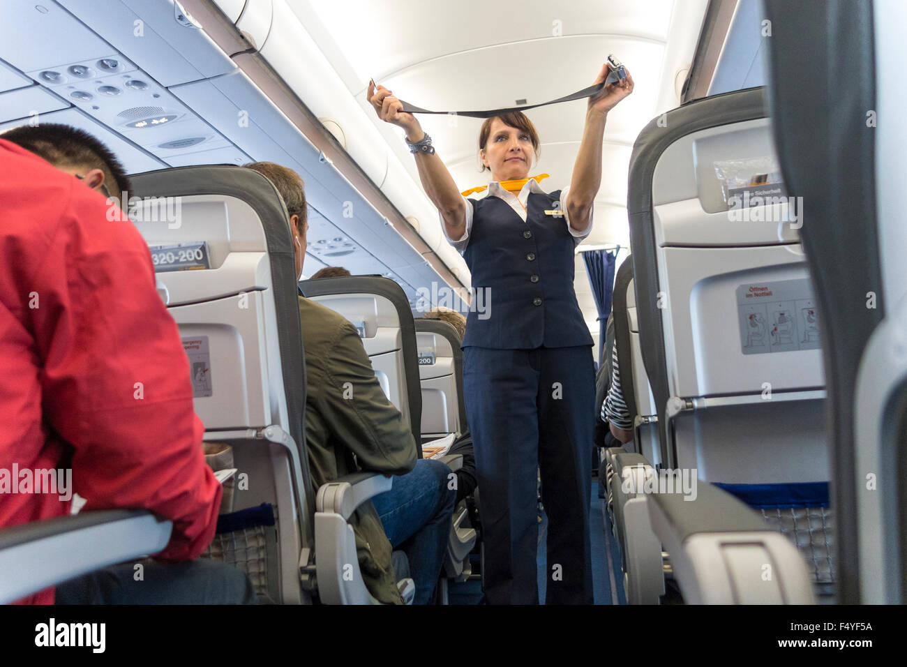 Female flight attendant demonstrating safety belt during safety instructions on Lufthansa plane - Stock Image
