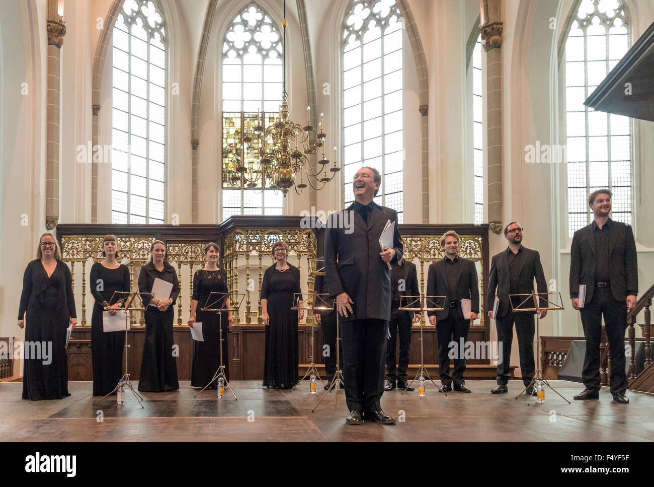 The Tallis Scholars with Peter Phillips on stage in a church. - Stock Image