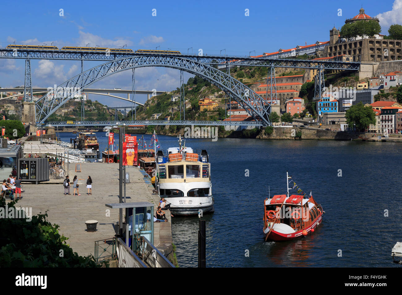 Cais de Ribeira River Douro and a light rail train crossng the Ponte Luis 1 bridge a World Heritage Site by UNESCO - Stock Image