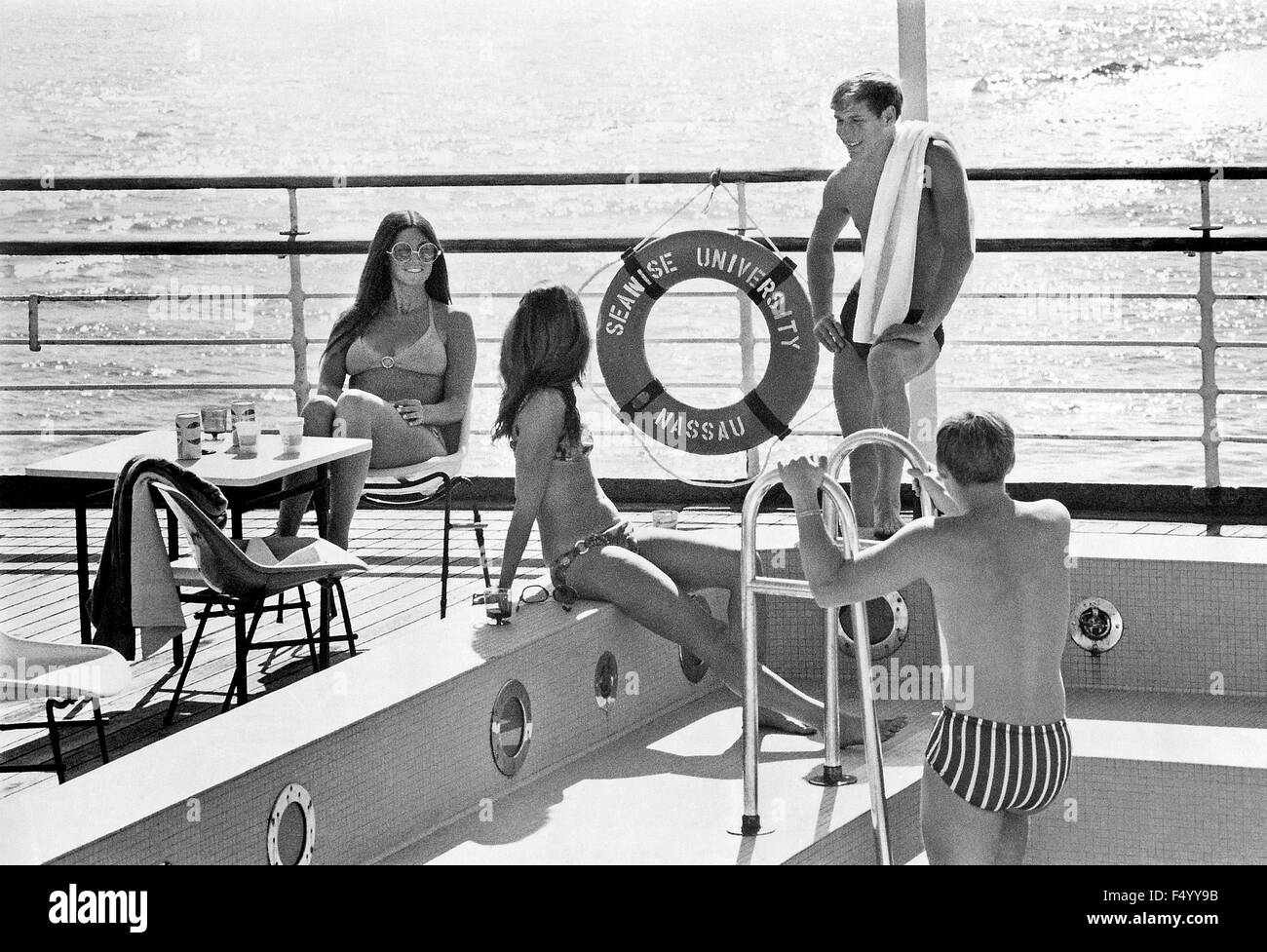 Young American students pose at the pool for publicity photos aboard Seawise University, the former RMS Queen Elizabeth, - Stock Image