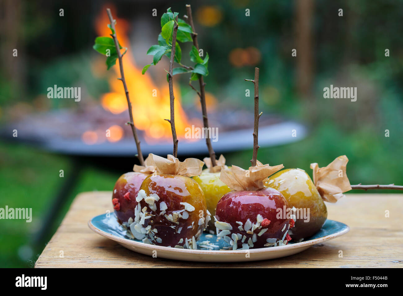 Toffee apples and a bonfire in the background - Stock Image
