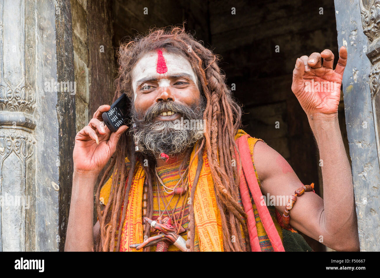 Sadhu, Holy Man, using his mobile phone opposite the burning ghats near Pashupatinath Temple - Stock Image