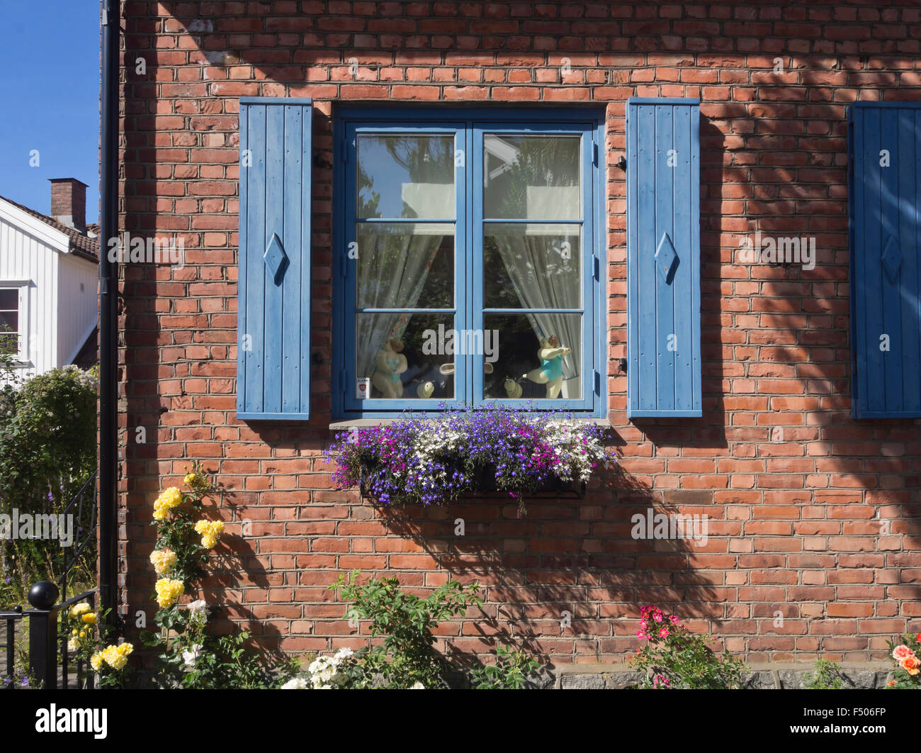Detail Of Idyllic Red Brick Cottage Blue Window Frame And