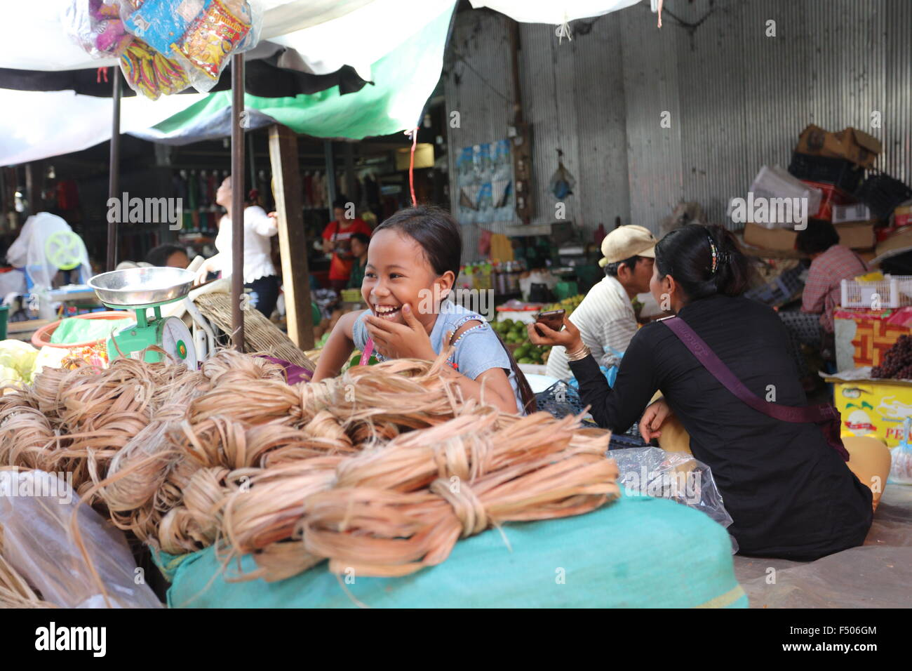 Laughing young Asian girl selling bast fiber on market - Stock Image