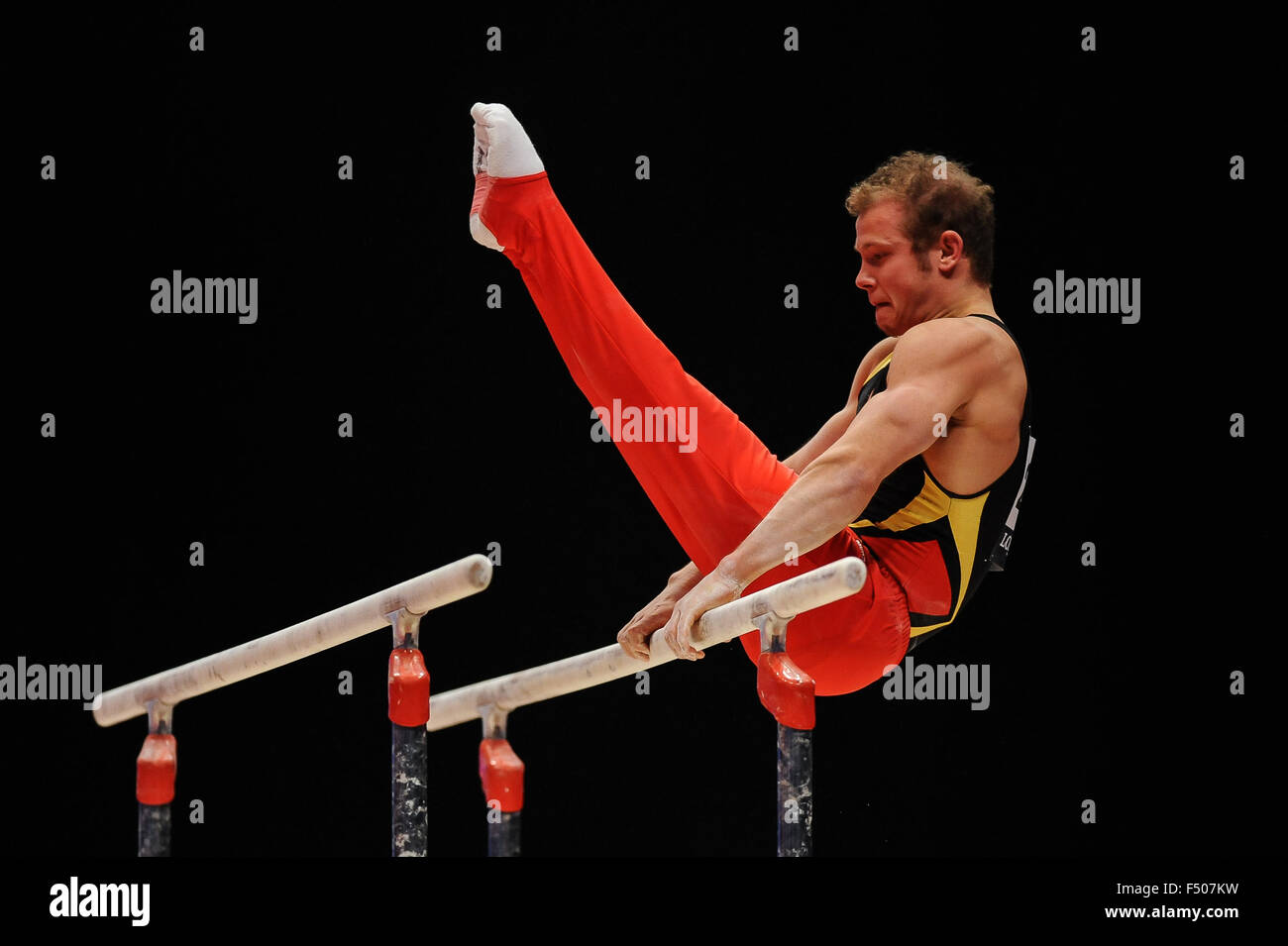 FABIAN HAMBUECHEN from Germany competes on the parallel bars during the preliminary round of the 2015 World Gymnastics - Stock Image