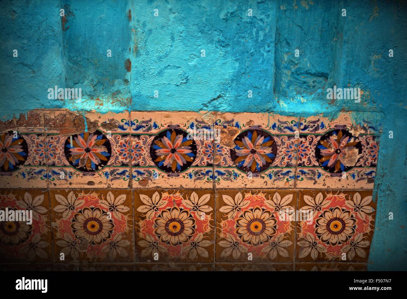 detail of colorful decorative tiles set in a bright blue wall of a Havana home in Cuba - Stock Image