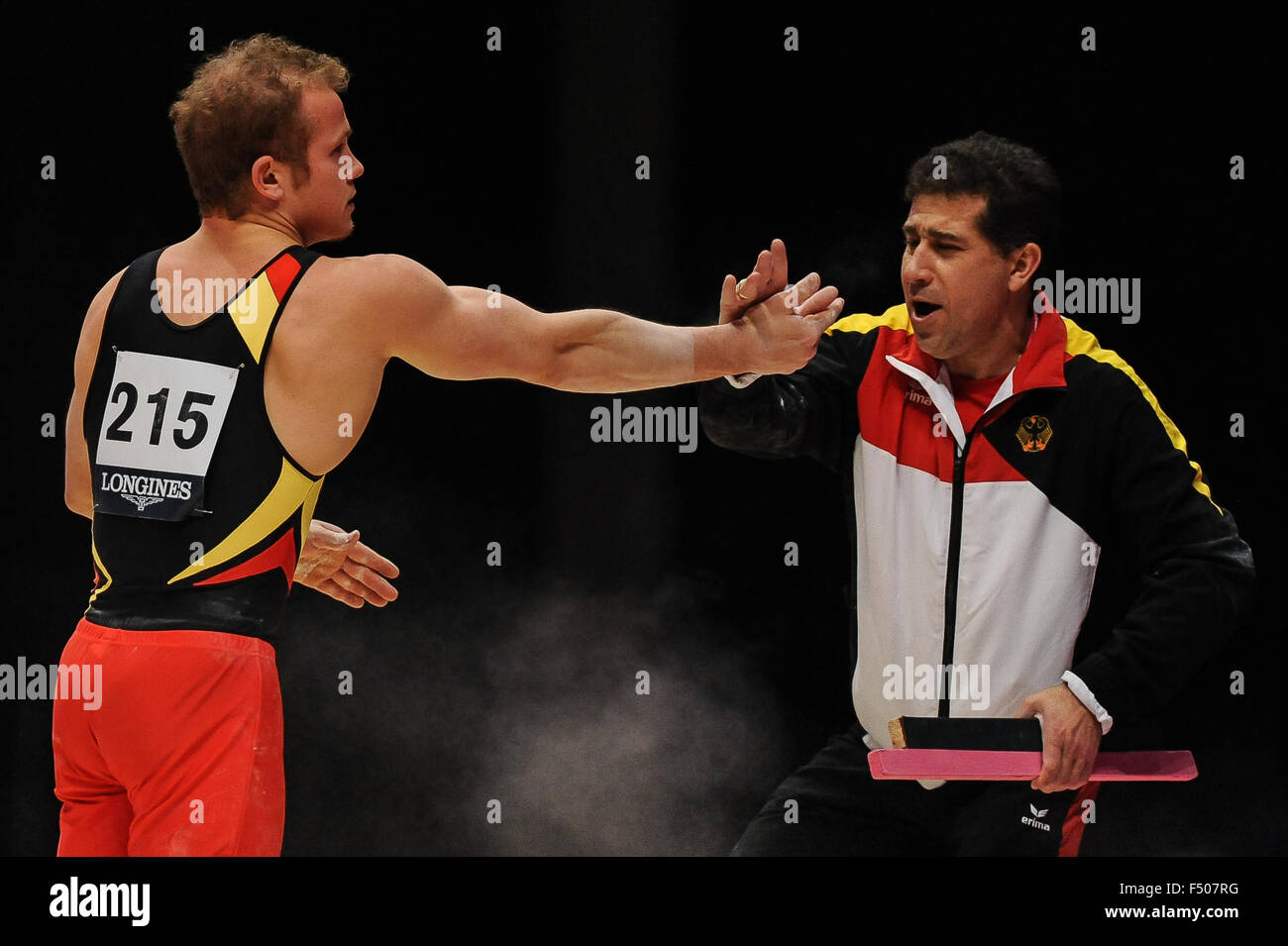 FABIAN HAMBUECHEN from Germany celebrates with his coach after his parallel bars routine during the preliminary - Stock Image