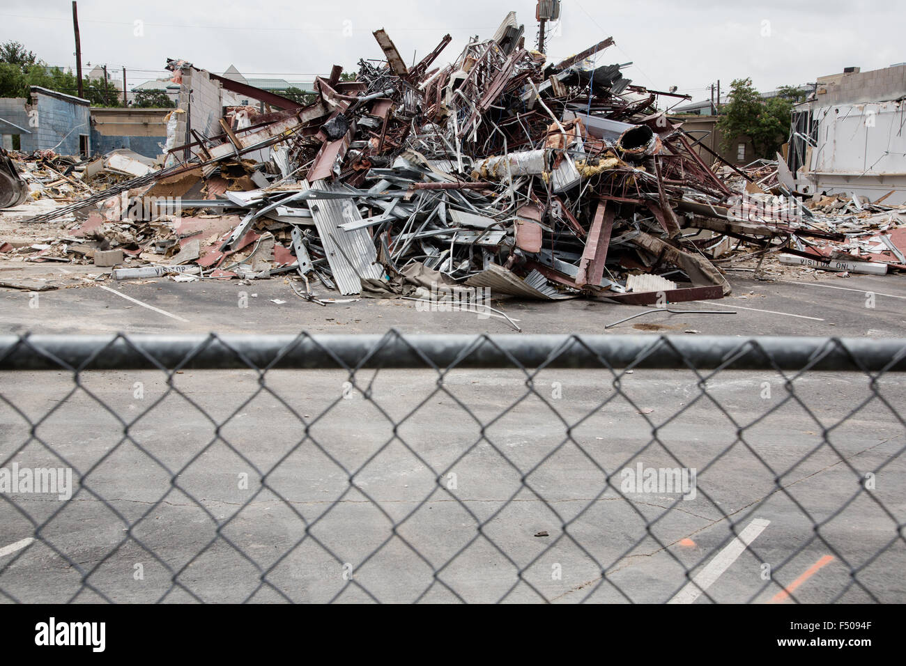 The rubble of a demolished building behind a chain link fence - Stock Image